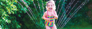 Girl enjoying summer under a sprinkler